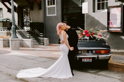 Fernanda bride hugging groom by black vintage car