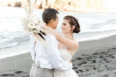 Stevie bride on black sand beach hugging groom