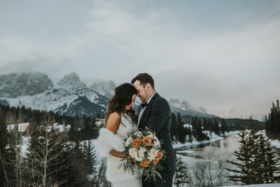 Winifred bride in snowy mountains holding bouquet with groom