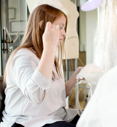 Woman sewing a part of a wedding dress by hand