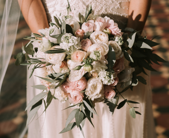 Vintage inspired wedding bouquet with pink and white roses accented by green leaves
