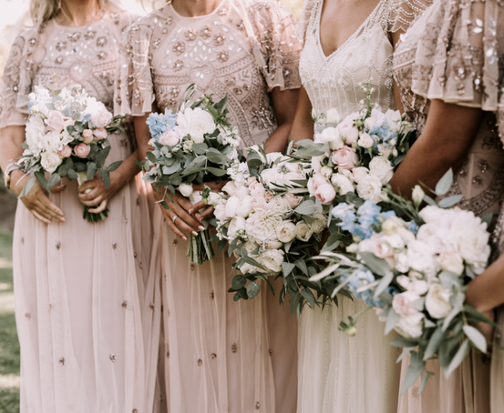 Vintage inspired bridesmaids dresses in blush color with white and pink rose bouquets